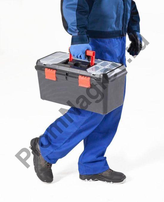 Переносной чемоданчик аварийного набора сорбентов в руках у работника, на пути к месту розлива опасных веществ.